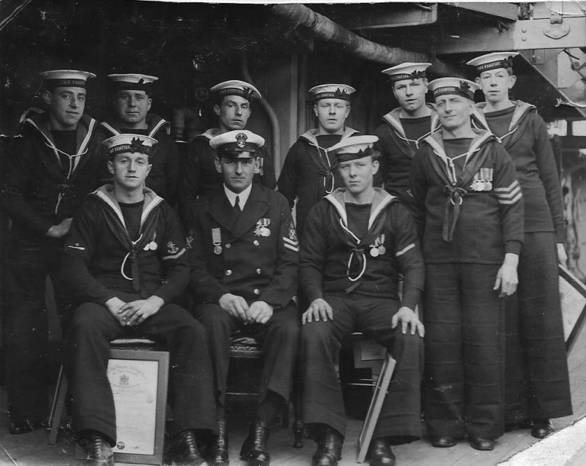 Sailors from HMS Vampire pictured with one of the framed RNLI certificates
